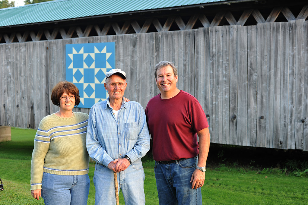Standing with the new barn quilt at the Graham Road covered bridge are (from left) Kathy McCarty, Bob Benson and Jeff Scribben.