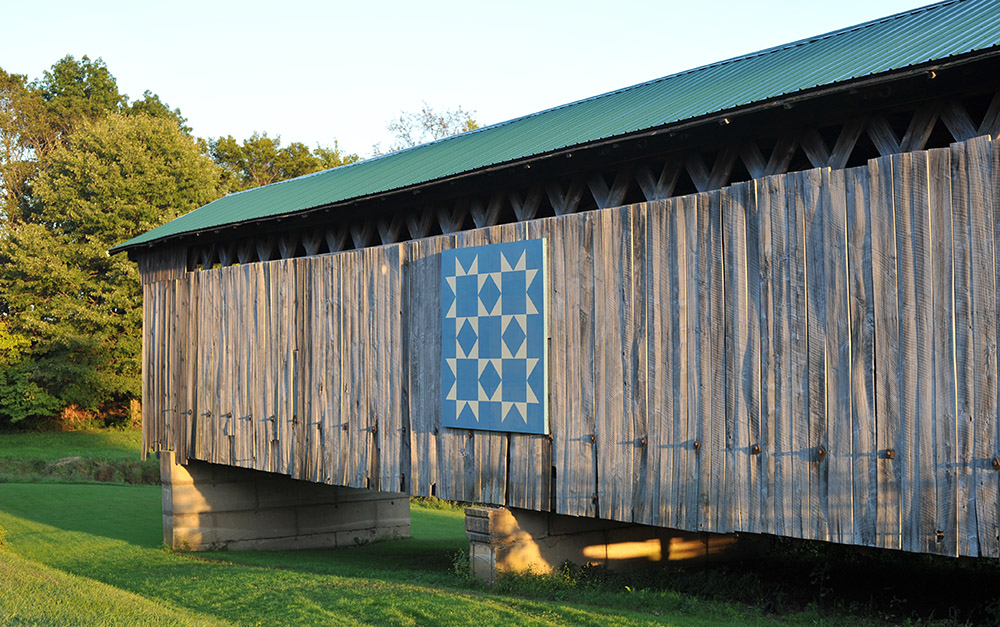 Graham Road, the center piece of an Ashtabula County Metro Park, sports an 8X8 barn quilt that honors the Benson family, which donated the land the covered bridge rests upon.