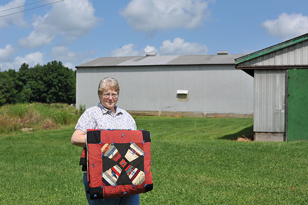 Lynn Moore holds the quilt that inspired the barn quilt.