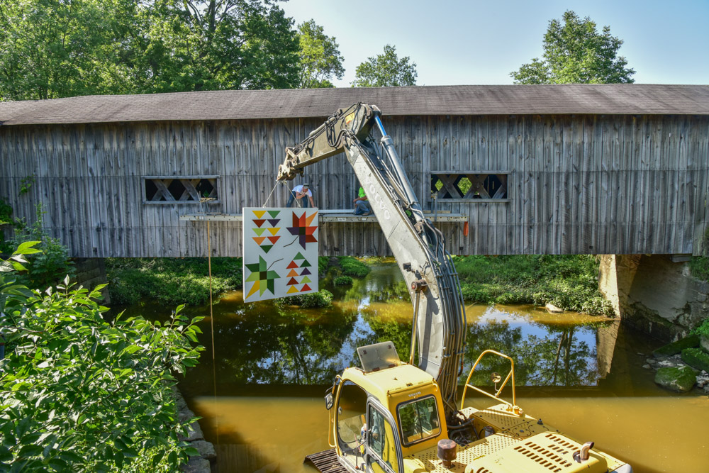 A track hoe had to be placed in Mill Creek in order to raise a barn quilt on the South Denmark Road covered bridge.
