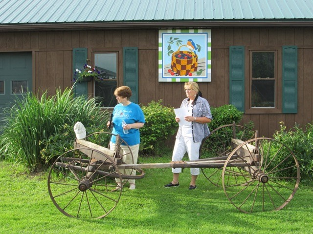 "Kathy McCarty, Barn Quilt Trail co-founder, ""says a few words"" during the dedication while Karla Gadley looks on."