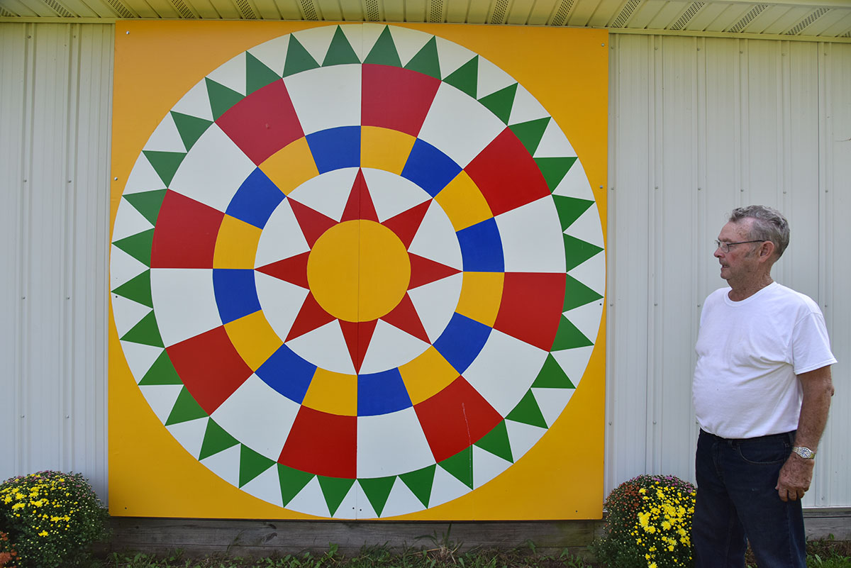 Gary Tabor stands next to the barn quilt he painted and installed on his toy museum in Williamsfield Township