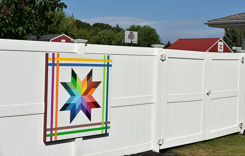 The Rainbow Star quilt on the fence is one of two BQ's at this address. The second (in background) is on the garage and may not be visible if the fence opening is closed. Both are 4-by-4 feet.