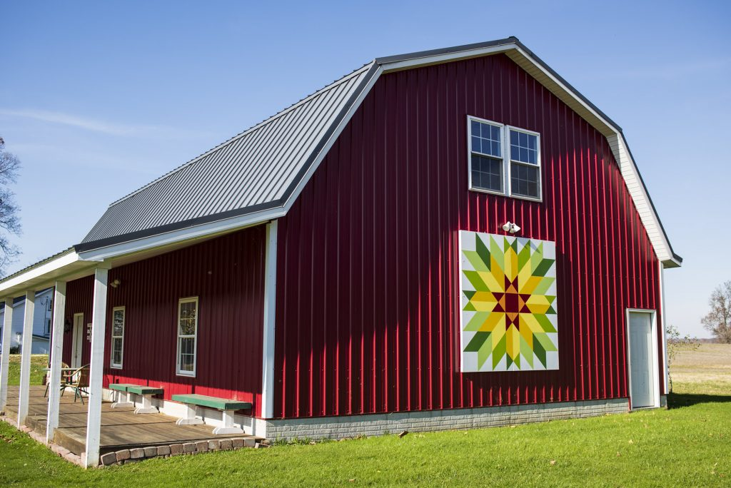 Barn quilt on side of red barn.